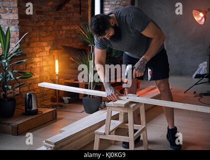 Carpenter drilling a hole in a board in a room with loft interio - Stock Photo