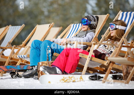Brother and sister sitting in sun loungers on ski terrain - Stock Photo