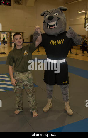 Sgt. Rocky, 3rd Infantry Division's mascot, holds up the arm of the fly weight class champion, Sgt. Brycen Minor, - Stock Photo