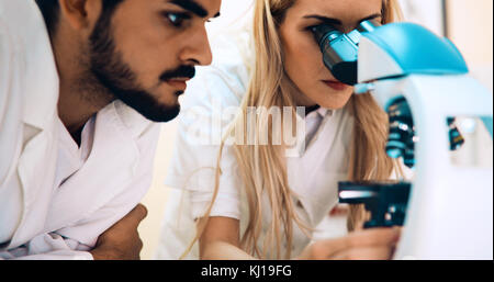 Group of scientists doing research looking through microscope - Stock Photo