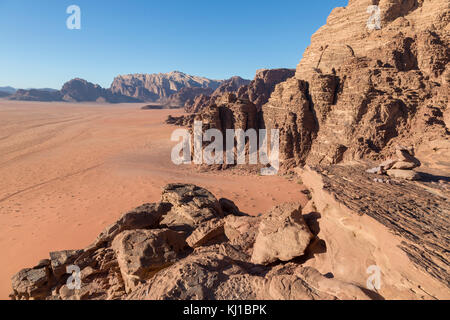 Reddish sand and rock landscapes in the desert of Wadi Rum, southern Jordan - Stock Photo