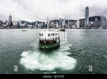 Star ferry on a cloudy sky with the famous Hong Kong island skyline from across the Victoria harbor in Kowloon in - Stock Photo