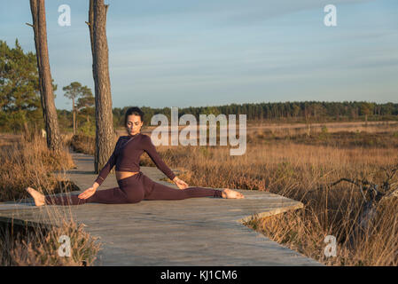 woman practicing yoga outside in open space in a nature reserve, doing the splits. - Stock Photo