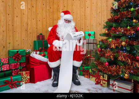 Santa Claus in his grotto surrounded by a Christmas tree with presents and gift wrapped boxes checking the Naughty - Stock Photo