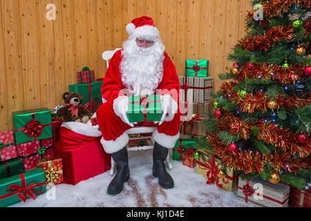 Santa Claus in his grotto surrounded by a Christmas tree with presents and gift wrapped boxes - Stock Photo