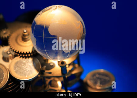 Glass globe lying on gears and coins on dark blue background - Stock Photo