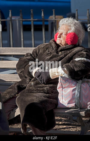 A senior citizen in a heavy coat sunning on a winter day in Father Demo Square in Greenwich Village, Manhattan, - Stock Photo