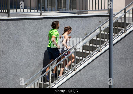 Young couple running upstairs in urban enviroment on summer day - Stock Photo