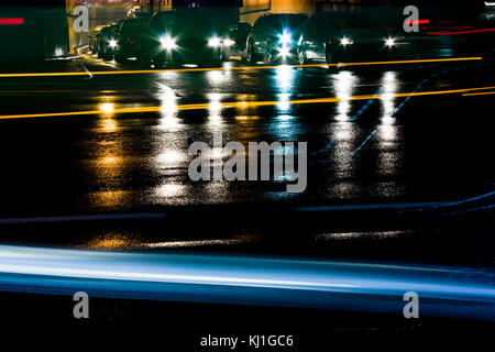 Night traffic on rainy city streets. Cars queued at tunnel exit waiting at intersection while driving vehicles moving - Stock Photo