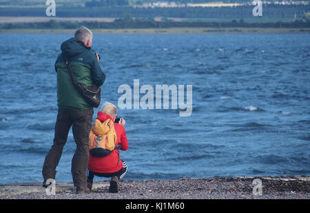 A couple photographing the sea at Cromarty Point, Scotlad - Stock Photo