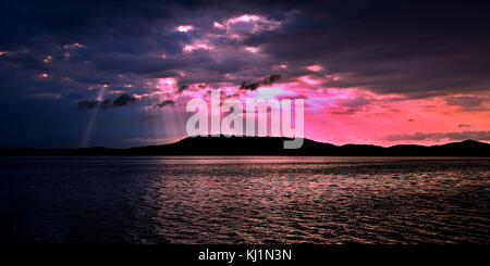Delightful inspirational brightly coloured cloudy sea water panoramic sunrise seascape featuring distinctive crepuscular - Stock Photo