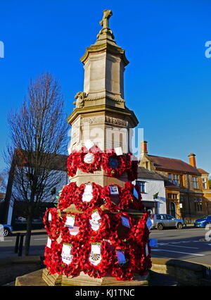War memorial in the town centre at Brackley, Northamptonshire England; covered with poppy wreaths for Rememberance - Stock Photo