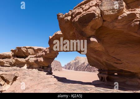 natural rock bridge and panoramic view of Wadi Rum desert, Jordan - Stock Photo