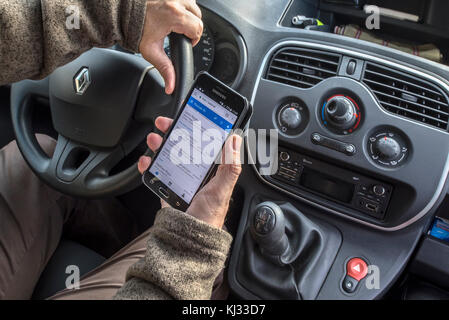 Irresponsible man at steering wheel checking messages on smart phone / smartphone / cellphone while driving car - Stock Photo