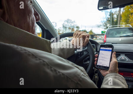 Irresponsible elderly man at steering wheel checking messages on smart phone / smartphone / cellphone while driving - Stock Photo