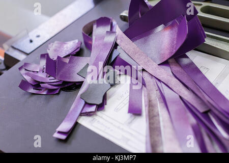 close-up of purple parts of handbags lying on the paper - Stock Photo