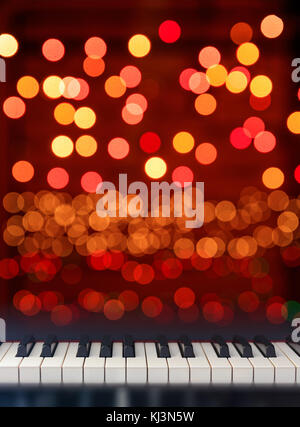 Classical Piano keyboard front view on Christmas lights bokeh background - Stock Photo