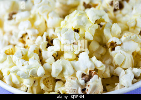 Popcorn in a bucket bucket is a top view on a dark wooden background. Macro shot from above - Stock Photo