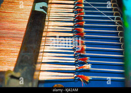 Close-up of tied thread ends of a saree on an automatic saree weaving machine. Belagavi, Karnataka, India - Stock Photo
