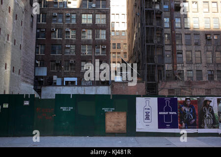 advertising on boarded up construction site in midtown Manhattan, New York City - Stock Photo