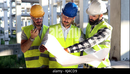Construction engineers discussion with architects at construction site - Stock Photo
