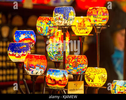 A display of coloured glass candle holders on display at a stall in the Edinburgh Christmas market. - Stock Photo