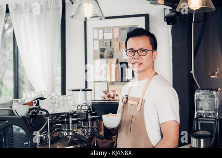 Male Barista cafe owner holding coffee cup in store counter bar inside coffee shop, food and drink business start - Stock Photo