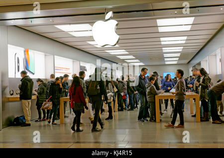 People browsing at electronic products in the Apple Pacific Centre store in the Pacific Centre Mall, Vancouver, - Stock Photo