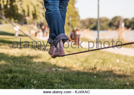 man's feet on low tight rope - Stock Photo
