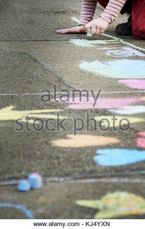 Child drawing with chalk on asphalt - Stock Photo