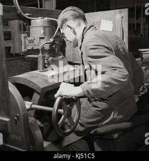 1950s, historical, male worker using a Fuller electric motor with drill and wheel to do precision metal  work, England, - Stock Photo