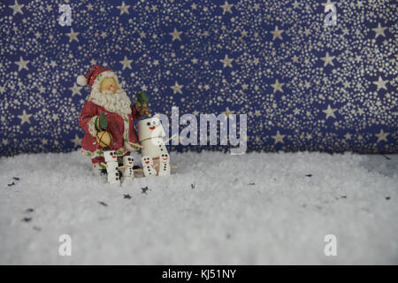 Christmas food photography image using marshmallows shaped as snowman with happy iced on smile and standing in snow - Stock Photo