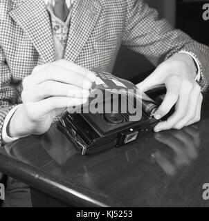 1950s, historical, young man loading negative roll film into the back of a film camera. This spool-wound photographic - Stock Photo