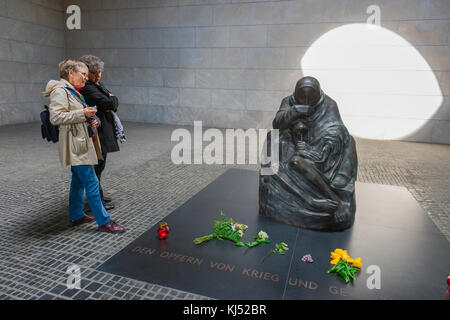 Neue Wache Berlin, tourists view the mother and son monument in the National Memorial To The Victims Of War And - Stock Photo