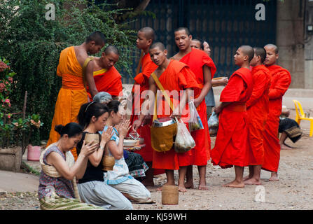 Buddhist monks receive alms each morning from local women, who thereby 'make merit' for themselves.  Pakse, Laos - Stock Photo