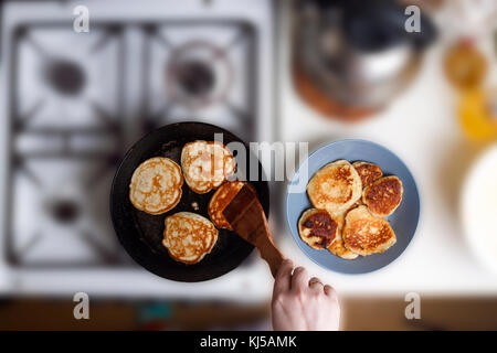 Woman fry pancakes in a frying pan on an old gas stove. Concept: Cooking, baking. View from above. Free space for - Stock Photo