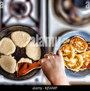 Woman fry pancakes in a frying pan on an old gas stove. Concept: Cooking, baking. View from above. top veiw - Stock Photo