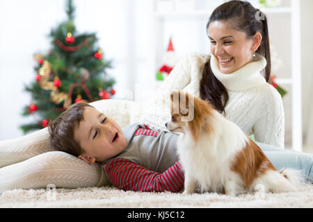 Portrait of a happy mother and her little son with dog spending together Christmas time at home near the x-mas tree - Stock Photo