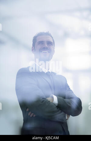 from behind the glass. modern businessman looks out the window of the office - Stock Photo