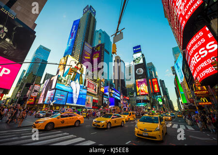 NEW YORK CITY - AUGUST 23, 2017: Bright neon signage flashes over crowds and taxi traffic zooming past Times Square - Stock Photo