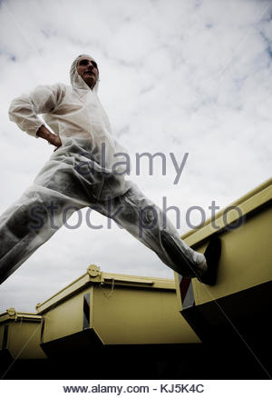 man in protective overall standing astride containers - Stock Photo