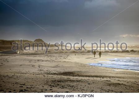 people on cloudy beach - Stock Photo