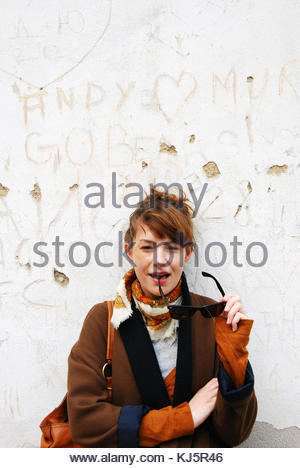 young woman with sunglasses by white etched wall - Stock Photo