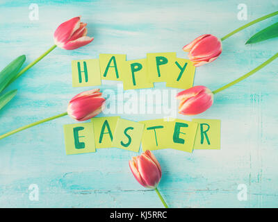 Happy Easter background tulips flowers hand written letters. Green pastel backdrop spring greeting card - Stock Photo