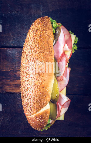 Big submarine sandwich with salami,cheese and pickles from above on wooden background,selective focus