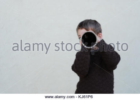 Portrait of a young boy looking through a tube hole - Stock Photo