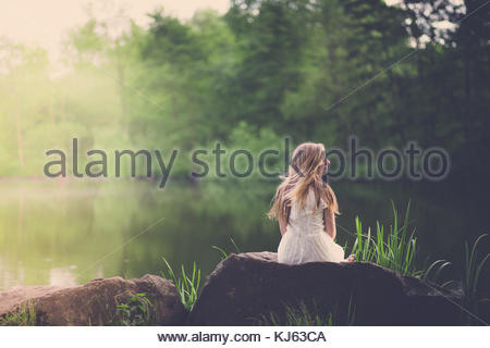 Blonde woman relaxes close to a pond - Stock Photo