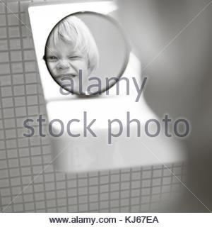 Little boy blinking in the mirror - Stock Photo
