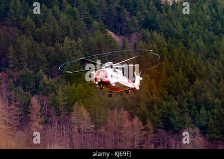 An HM coastguard Sikorsky S92 helicopter searches for a missing walker close to Inverness in the Scottish Highlands. - Stock Photo