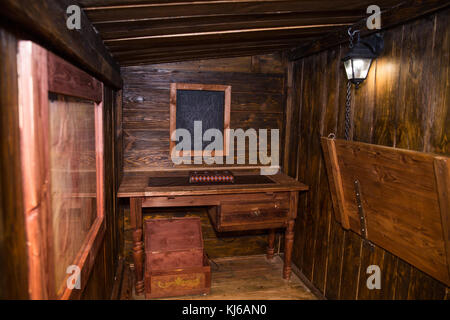 Interior Of Old Ship Cabin With Wooden Panels And Cords Lantern Chest Table